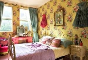 This vintage inspired, ultra feminine bedroom reminds me of Betsey Johnson - the Queen Bee of boho fashion - every time I see it - from the flirty tulle frocks on the wall, hot pink french chic furniture to the bold yellow and big floral wallpaper.
